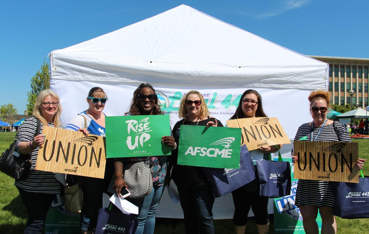 A group of public employees pose with pro-union signs in front of a tent.
